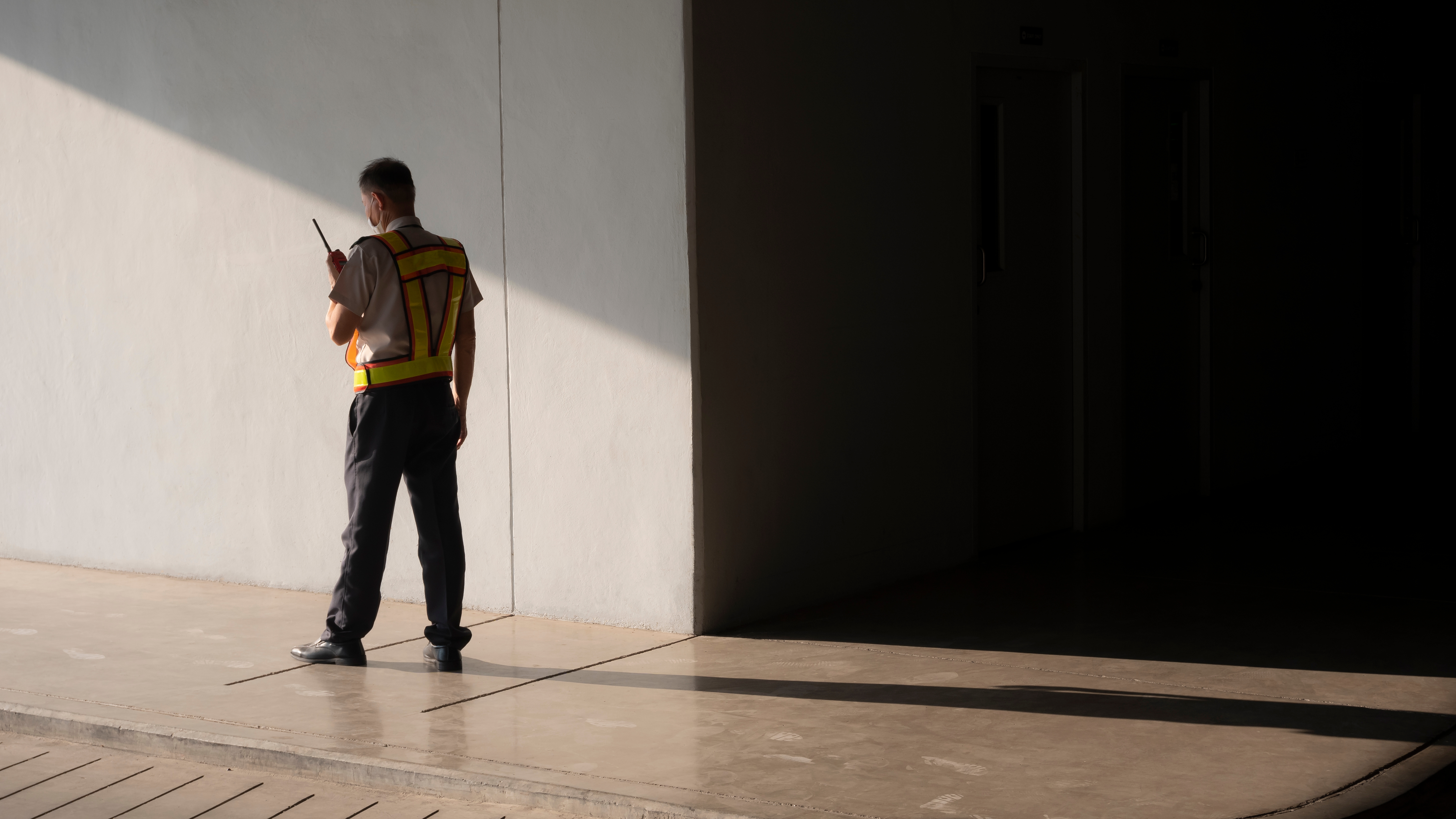 asian-security-guard-in-safety-vest-walking-on-side